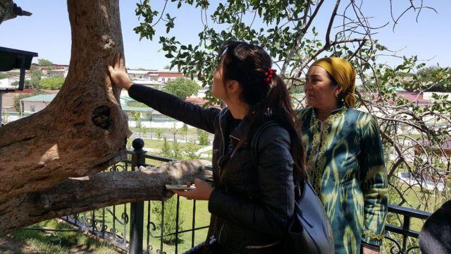 Dilrabo (com lenço) e sua filha tocando árvore de pistache