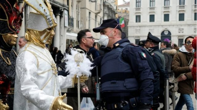 Police officer wearing a protective face mask stands next to carnival revellers at Venice Carnival