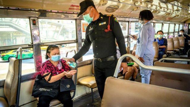 Quân đội Thái Lan phát thuốc khử trùng tay và kiểm tra nhiệt độ của hành khách trên một chuyến xe buýt đi qua một trong những trạm kiểm soát tại Bangkok