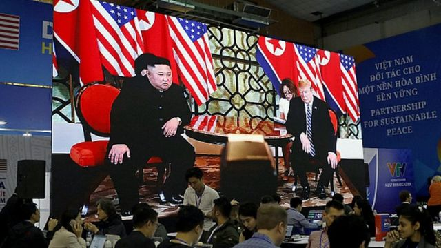 Journalists work next to a large screen displaying news reporting on the second US-North Korea Summit, at the international media centre, in Hanoi, Vietnam, 28 February 2019