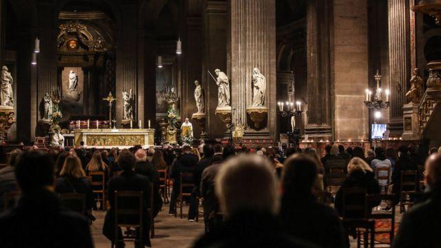 مراسم نیمهشب در کلیسایی در پاریس. مردم فرانسه اجازه خروج از منزل بعد از هشت شب را ندارند. مراسم کریسمس از این قاعده استثنا بود. شرکتکنندگان با فاصله از هم نشستهاند