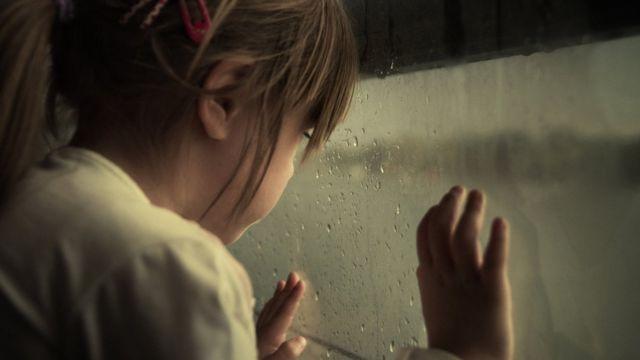 camdan bakan bir kız çocuğu
