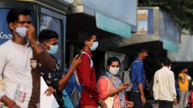Gente en India con mascarilla esperando un autobús
