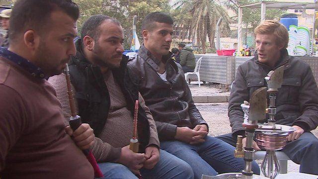 Thomas Fessy (R )discusses tensions between Iran and Saudi Arabia at a cafe in Baghdad