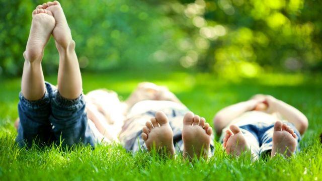 Tres personas de pies descalzos tumbadas en la hierba.