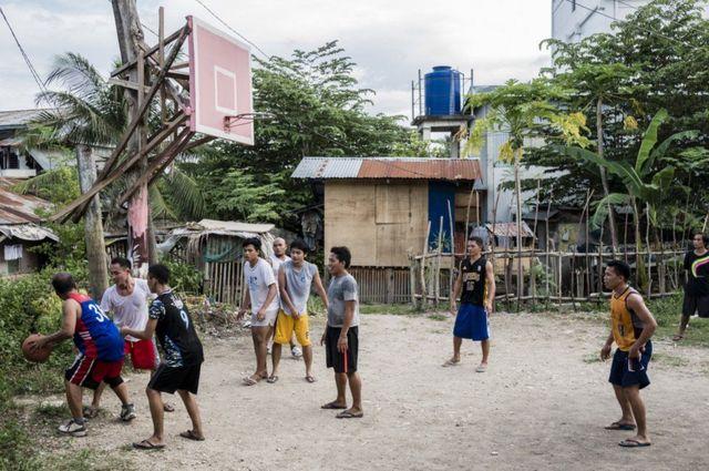شباب يلعبون السلة، بعضهم يرتدي ملابس رياضية