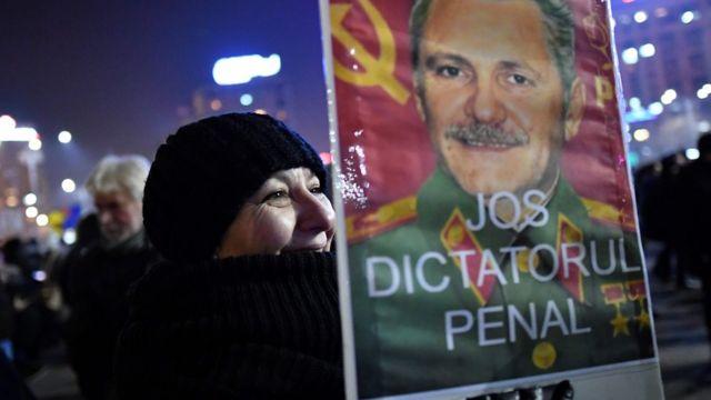 Una mujer protesta en Rumania con un cartel en contra de Liviu Dragnea