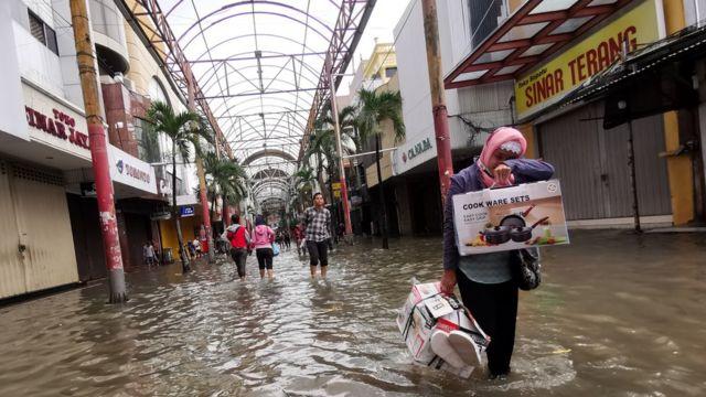 Warga melintasi banjir menggenangi pertokoan Pasar Baru, Jakarta Pusat, Selasa (25/02)