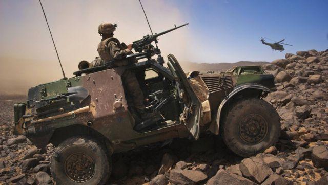 مركبة عليها جندي ومدفع رشاش وطائرة هليكوبتر في منطقة جبلية