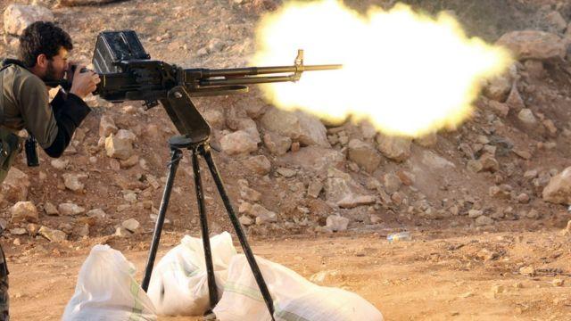 عنصر من المعارضة يضرب قذيفة مدفعية
