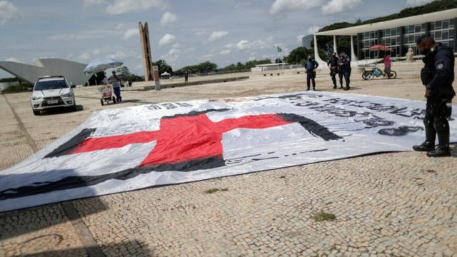 Policial observando bandeira com símbolonazista com imagem de Bolsonaro