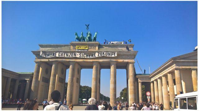 "Abigaragambya 15 bamaze hafi isaha hejuru y'inyubako ya Brandenburger Gate bafite ibyapa byanditseho ngo ""Umutekano ku mipaka, shaka ejo heza"""