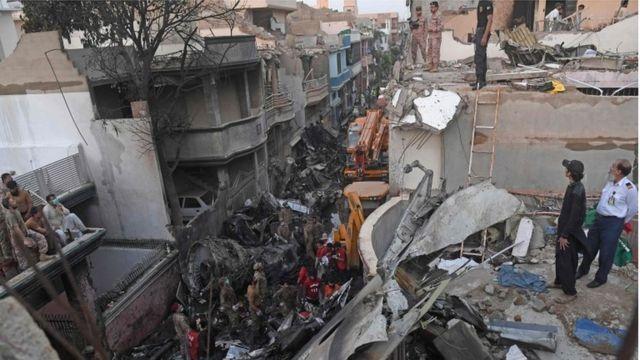 Funcionários de resgate olhando a área destruída