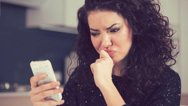Mulher olha para celular com uma expressão de insatisfação