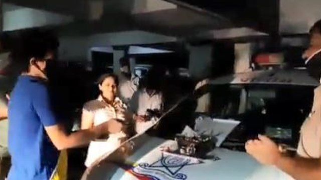 Vatsal Sharma cuts a cake while police officials sing to him