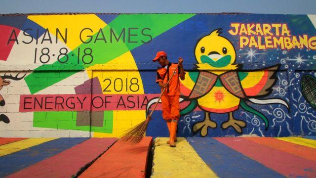 Petugas kebersihan menyapu dengan latar belakang mural Asian Games 2018 di Kampung Tematik, Kemayoran, Jakarta.