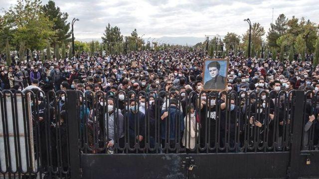 تصویری از روز خاکسپاری آقای شجریان که مردم را پشت میلهها نشان میداد
