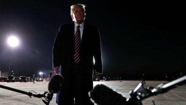Trump em pé em pista, aparentemente de aeroporto, durante a noite e em frente a dois microfones