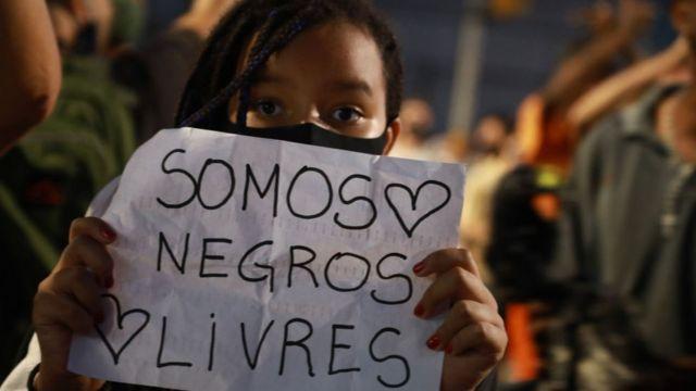 Mulher segura carta escrito 'Somos negros livres' durante protesto