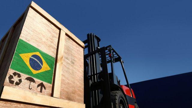 Trator carrega caixa com bandeira do Brasil