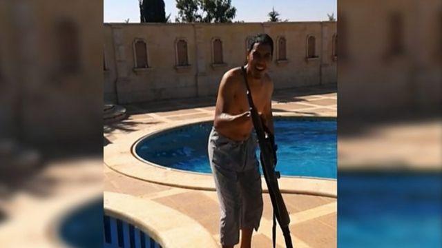 Choukri Ellekhlif posando à beira de uma piscina com uma arma nas filmagens do smartphone