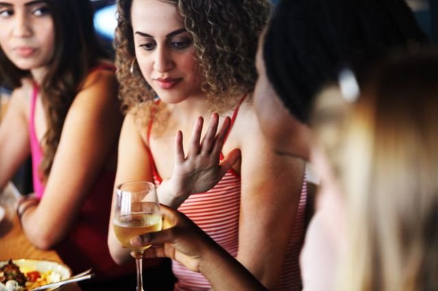 Una mujer rechaza una copa de vino