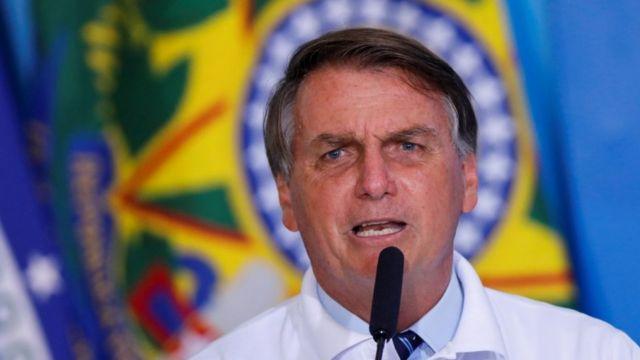 Bolsonaro fala ao microfone, com bandeira atrás