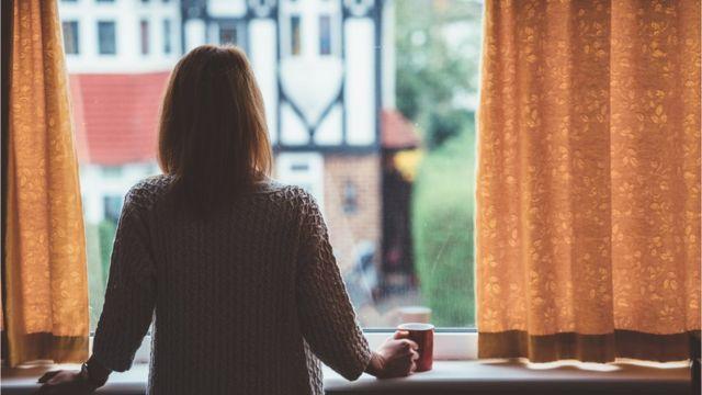 Mulher de costas na janela observando a rua