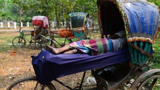 প্রচণ্ড গরমে কাজ বন্ধ রেখে বিশ্রাম নিচ্ছেন একজন রিক্সাচালক