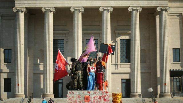 Активисты на постаменте статуи