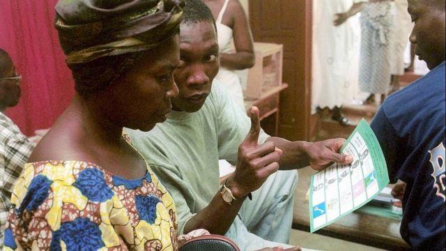 Un volontaire explique à une femme qu'elle peut valider son bulletin en signant ou posant ses empreintes lors de l'élection présidentielle de 2000 en Côte d'Ivoire.