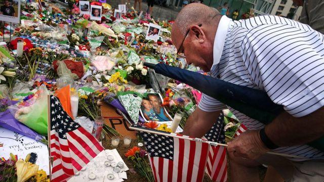 オーランド乱射事件の犠牲者を追悼する祭壇に米国旗を飾る男性(19日、米フロリダ州)