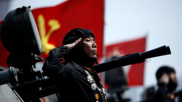 North Korean soldier saluting in front of a flag