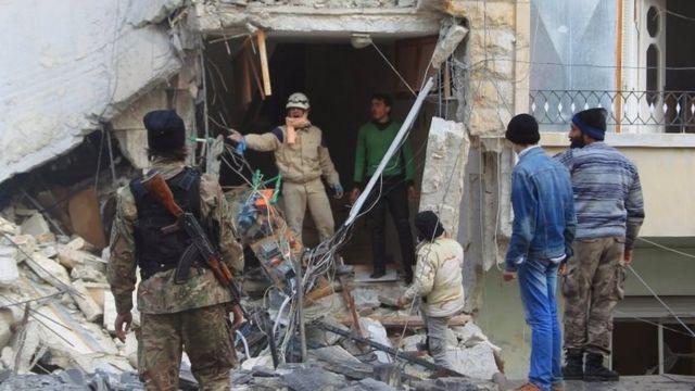 瓦礫の間に生存者を探す民間防衛隊