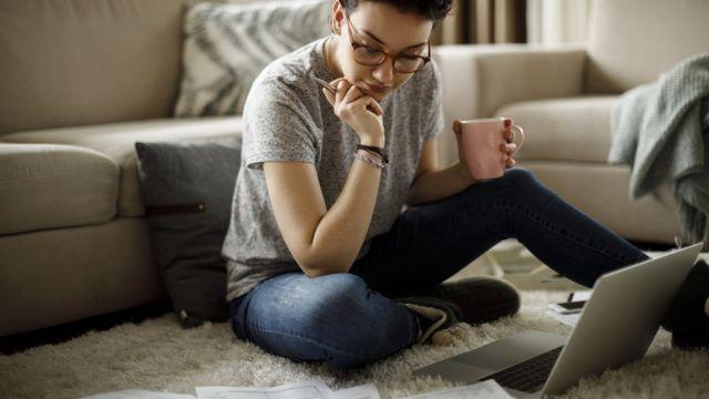 Mujer con taza en la mano, computadora y pensando.