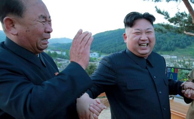 North Korean leader Kim Jong Un (R) reacts with Ri Pyong Chol (L) in this undated photo