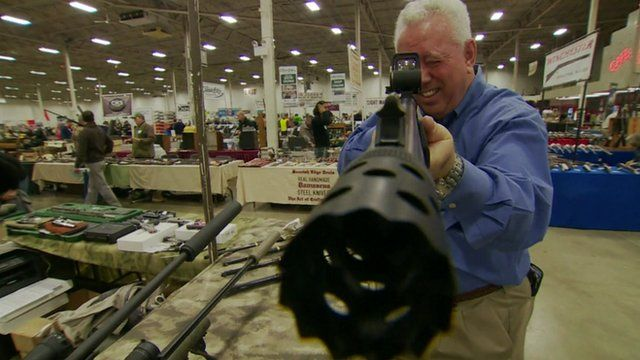 Man holding a gun for sale at a US gun show