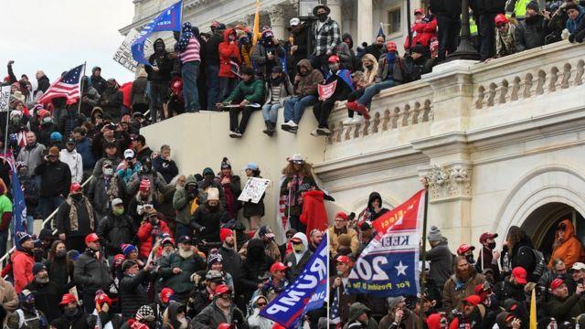 Um grupo de apoiadores de Donald Trump nos portões do Capitólio de Washington