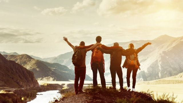 Four happy friends dey look mountains andget fun togeda