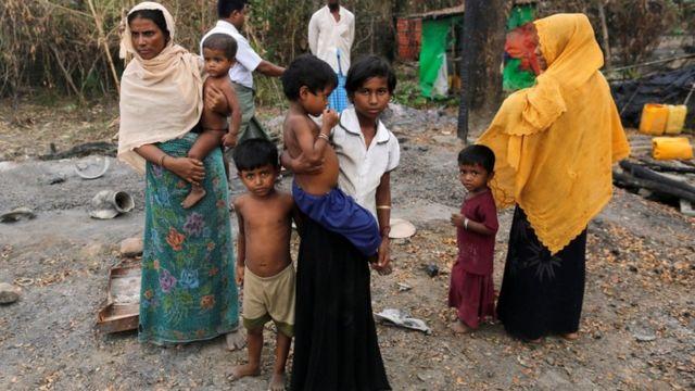 أسرة من مسلمي الروهينغا تقف إلى جانب بقايا كوخ تعرض للحرق