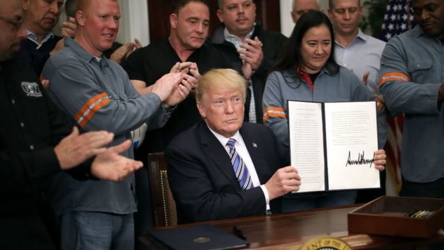特朗普举着签署的关税备忘录