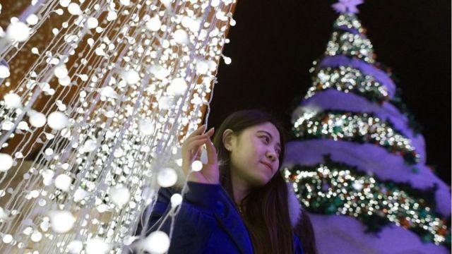 2018年12月22日,北京一名女士在圣诞树旁自拍。