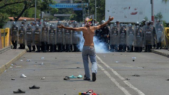Một người biểu tình đứng trước vệ binh quốc gia Venezuela ở Cucuta, Colombia