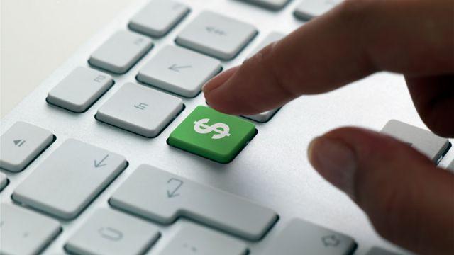 Mano sobre un teclado con el símbolo de dólar