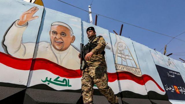 Um membro das forças iraquianas passa por um mural que retrata o Papa Francisco acenando ao lado de uma bandeira nacional iraquiana, em Bagdá