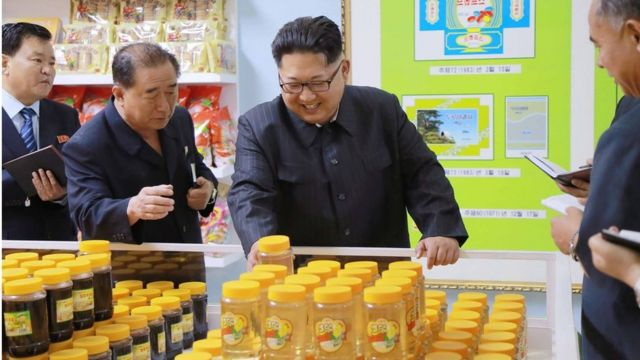 Image released by KCNA on 16 June 2016 showing North Korean leader Kim Jong-un (centre) surrounded by other officials taking notes, as he smilingly inspects products in the Pyongyang cornstarch factory.