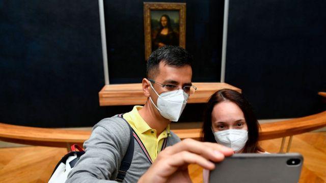Pessoas tirando selfie em frente à a Mona Lisa no Museu do Louvre