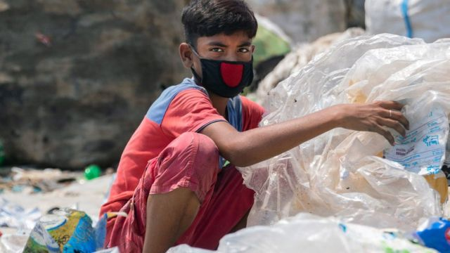 صبي يرتدي قناعاً للوجه يبحث في القمامة عن أشياء قد يستفيد منها. بنغلاديش