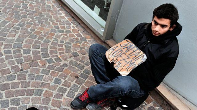Un joven pide dinero en la calle en Francia.