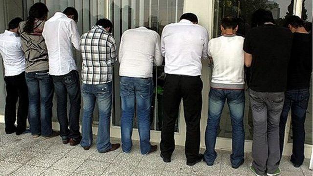 عکسی از چند مرد که پشت به دوربین و در حالت بازداشت ایستادهاند